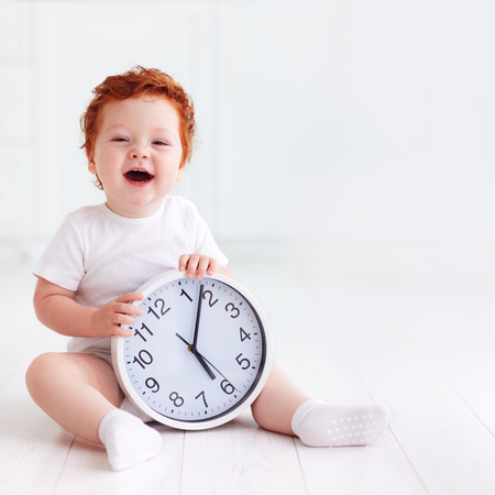 szczęśliwy mały maluch dziecko gospodarstwa koło zegara