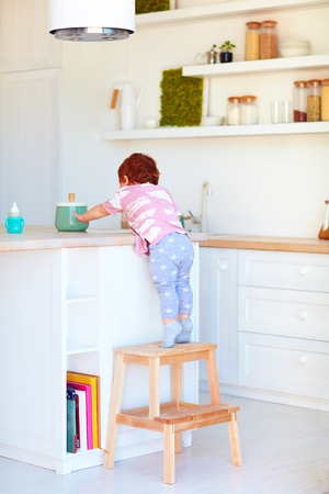 cute toddler baby climbs on step stool, trying to reach things on the high desk in the kitchen Stock Photo
