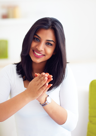 beautiful, happy indian woman with greeting gesture