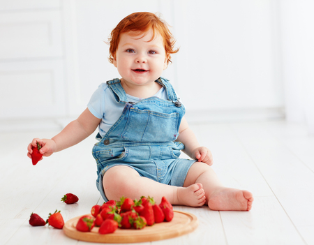 cute ginger toddler baby tasting strawberries Stock Photo - 83530461