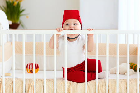 funny baby bites his cot as teeth are pricked Stock Photo