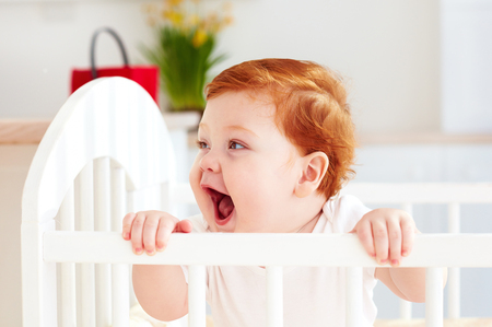 poprtait of cute happy infant baby standing in a cot at home Stock Photo