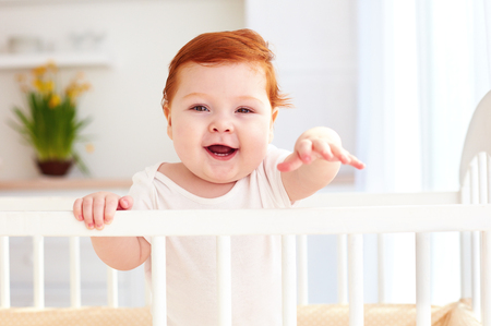 portait: poprtait of cute happy infant baby standing in a cot at home Stock Photo