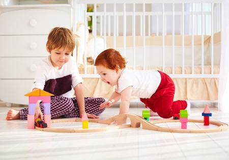 happy kids, brothers playing together with wooden toy railway in nursery room photo