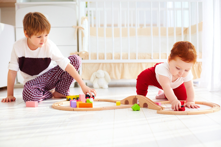 cute kids, brothers playing together with wooden toy railway in nursery room photo