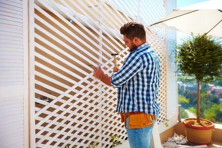 young adult man decorating the house wall, by setting up the wooden trellis for climbing plants