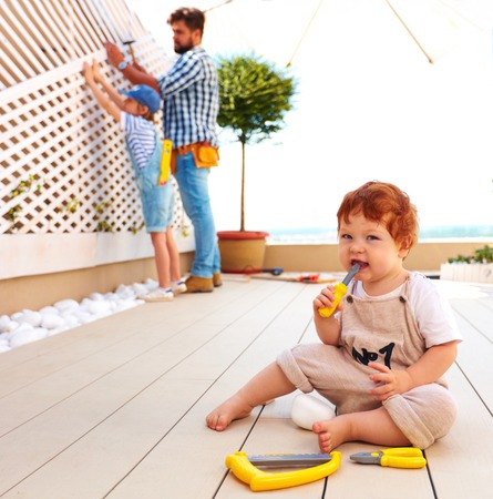 cute toddler baby helping his family with renovation