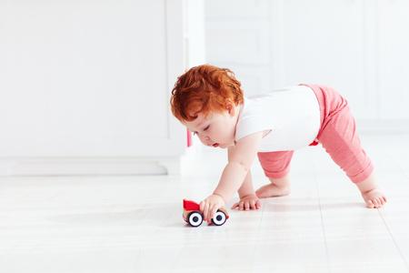 귀여운 빨간 머리 아기 소년 바닥에 장난감 자동차 압연