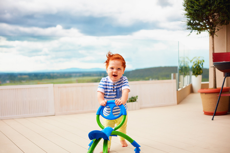 a toddler baby boy pushing pushing go cart, outdoors Stock Photo
