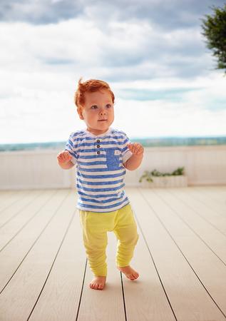 portrait of cute redhead, one year old baby boy walking on decking
