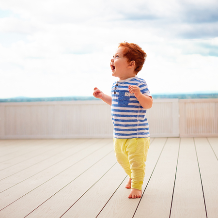 portrait of cute redhead, one year old baby boy walking on decking