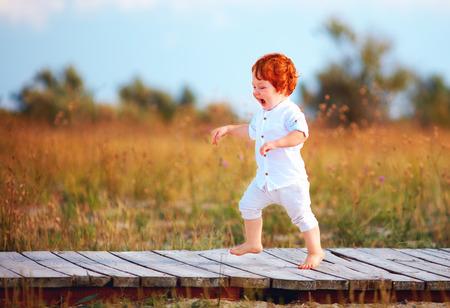 happy toddler baby running the path on summer field Foto de archivo