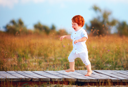 happy toddler baby running the path on summer field Standard-Bild