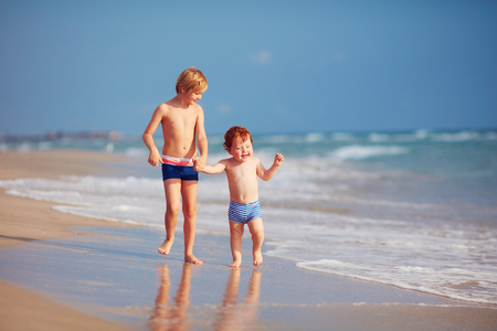 two brothers, cute kids having fun on sandy beach