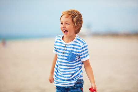 young delighted boy, kid playing with a toy propeller, having fun on summer beach