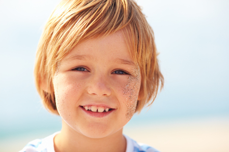 summer portrait of handsome boy face with freckles and sand on sunny day
