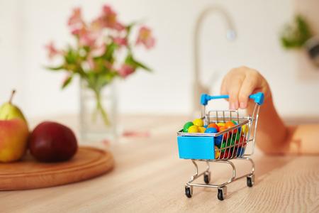 mini winkelwagentje vol snoepjes op keukenbureau