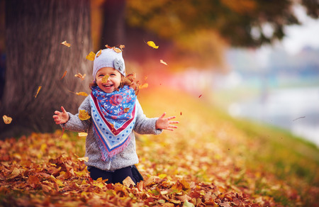 adorable happy girl throwing the fallen leaves up, playing in the autumn park