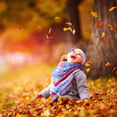 가을 공원에서 놀고 사랑 스럽다 행복한 아기 소녀 타락한 잎을 잡기 스톡 콘텐츠 - 87095653
