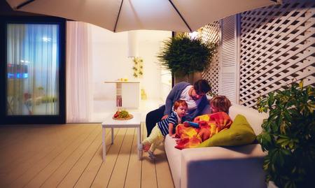 Familia relajante en zona de patio con cocina de espacio abierto y puertas correderas en el fondo Foto de archivo - 87406348