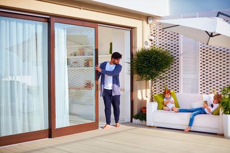 familia relajante al aire libre en el patio de la azotea con cocina abierta y puertas correderas