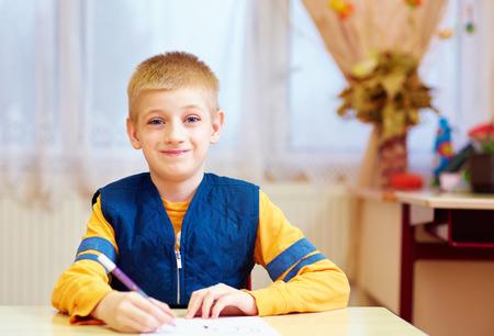 schattige jongen met speciale behoefte aan de balie in de klas zitten Stockfoto