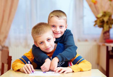 2 つのかわいい子供たちは、特別なニーズを持つ子供のためのリハビリテーション学校で友達