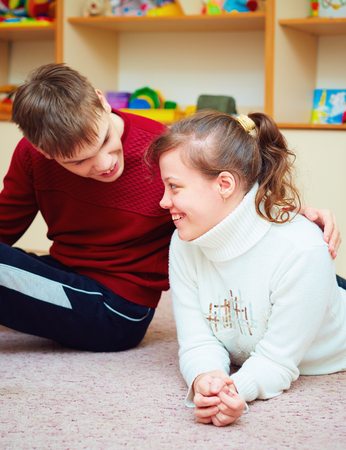 smiling teenage friends with special needs talking cheerfully together in rehabilitation center