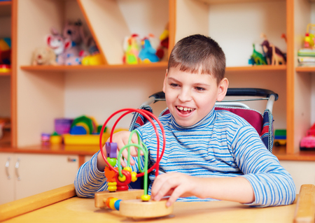 cheerful boy with disability at rehabilitation center for kids with special needs, solving logical puzzle Standard-Bild