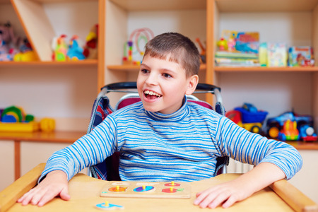 cheerful boy with disability at rehabilitation center for kids with special needs, solving logical puzzle Stock Photo