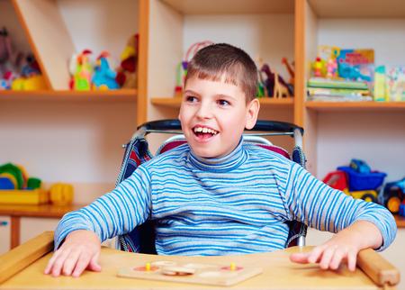 特別なニーズを持つ子供のためのリハビリテーションセンターで障害を持つ陽気な少年, 論理パズルを解く 写真素材