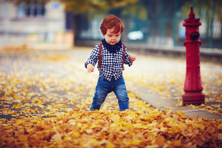 cute fashionable redhead baby boy walking on autumn street Stock Photo