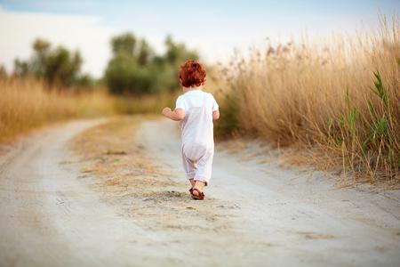 schattige peuter babyjongen weglopen langs het pad in de zomer veld