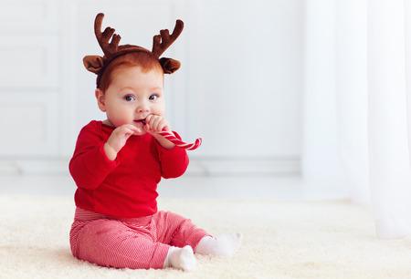 cute little redhead baby boy with reindeer band tasting christmas sweet treats, sitting on the floor at home Stockfoto