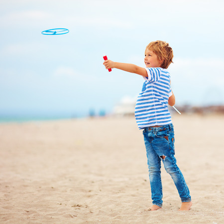 delighted cute young boy, kid having fun on beach, playing with propeller toy
