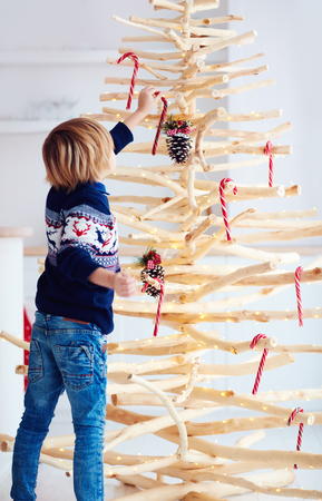 cute boy, kid decorate handcrafted christmas tree made of driftwood at home