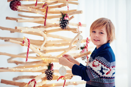 cute boy, kid decorate handcrafted christmas tree made of branches and driftwood at home