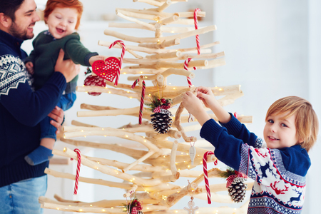family decorates an extraordinary christmas tree made of branches and driftwood at home Stock Photo