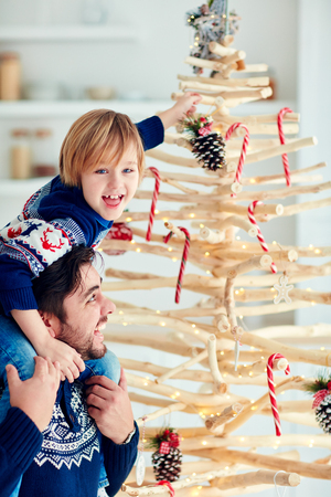happy father and son decorate eco-friendly christmas tree made of branches that were cut off during sanitary work Stock Photo