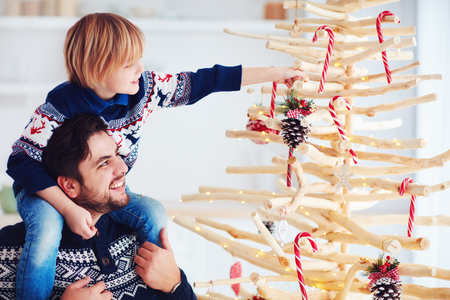 happy family, father and son decorate handcrafted christmas tree made of driftwood at home Stock Photo