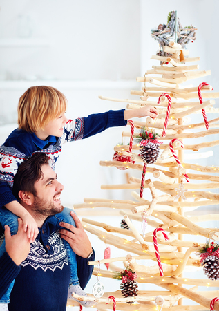 happy father and son decorate an extraordinary christmas tree made of branches and driftwood at home Stock Photo