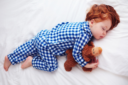 adorable redhead toddler baby sleeping with plush toy in flannel pajamas Stockfoto