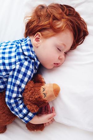 schattige roodharige peuter baby slaapt met knuffel in flanellen pyjama's Stockfoto