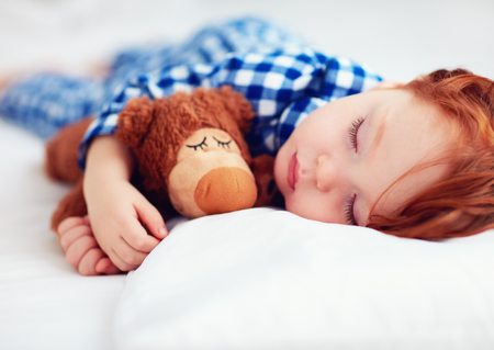 adorable redhead toddler baby in flannel pajamas sleeping with plush warmer toy Stock Photo