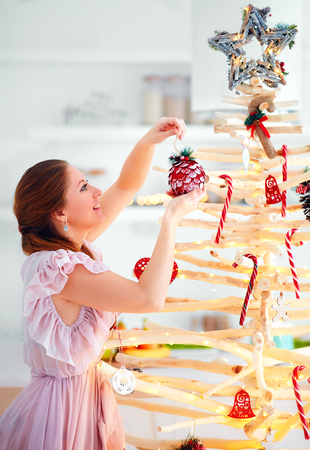 young woman decoration extraordinary, eco friendly christmas tree made of branches, winter holidays