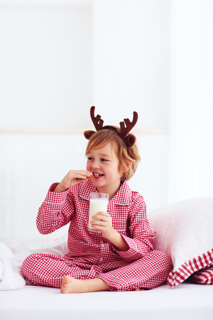 cute happy boy, kid in traditional flannel pajamas sitting on the bed with glass of fresh milk and cookies, christmas holidays