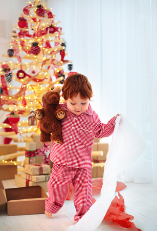 cute happy toddler boy in pajamas has got his present on christmas