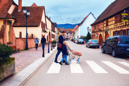EGUISHEIM, ALSACE, FRANCE - DECEMBER 24, 2017: cute family crossing the street of medieval village Editorial