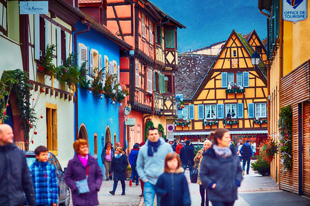 EGUISHEIM, ALSACE, FRANCE - DECEMBER 24, 2017: Tourists are walking along the Grand-Rue street, among colorful half-timbered houses Editorial