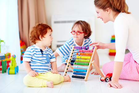Cheerful young woman. Mother playing games with kids at nursery room Stock Photo - 92821546